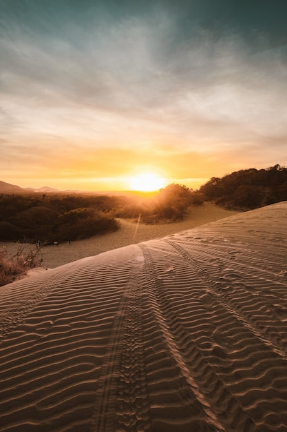 Vertical shot of sandy hills in a desert with the breathtaking sunset Free Photo