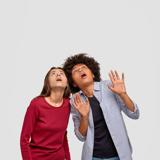 Vertical shot of scared best friend raise heads, have stupefied look at ceiling, afraid of heavy thing falling down, keep hands in protective gesture, dressed in fashionable clothes, isolated on white Free Photo