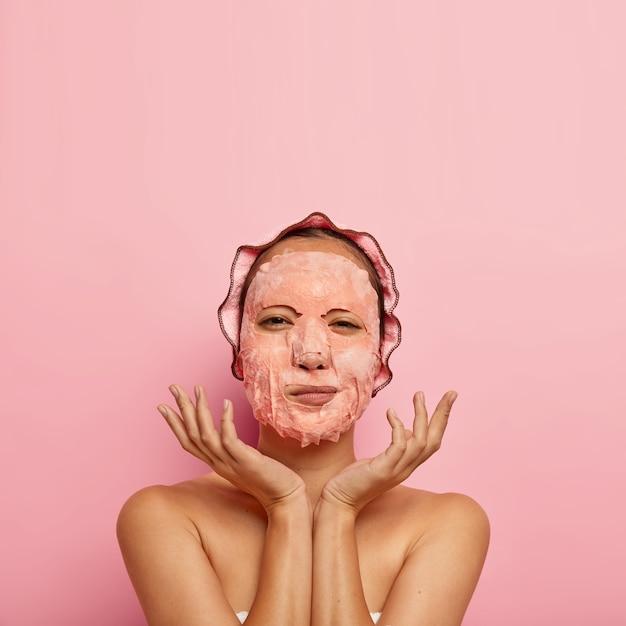 Colpo verticale del modello femminile serio con maschera facciale in foglio, allarga i palmi vicino al viso, ha una routine di bellezza a casa la sera, indossa la cuffia da bagno, sta nudo, isolato sul muro rosa, spazio vuoto sopra Foto Gratuite