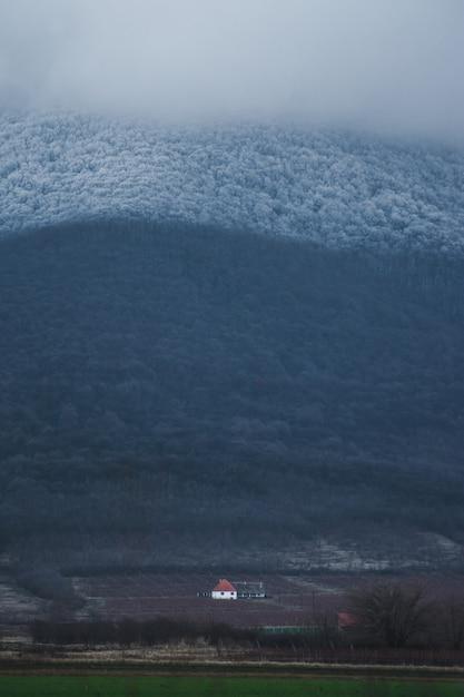 Colpo verticale di una casa singola nella valle sotto la montagna Foto Gratuite