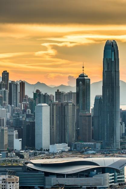 Colpo verticale dei grattacieli di hong kong sotto un cielo arancione al tramonto Foto Gratuite
