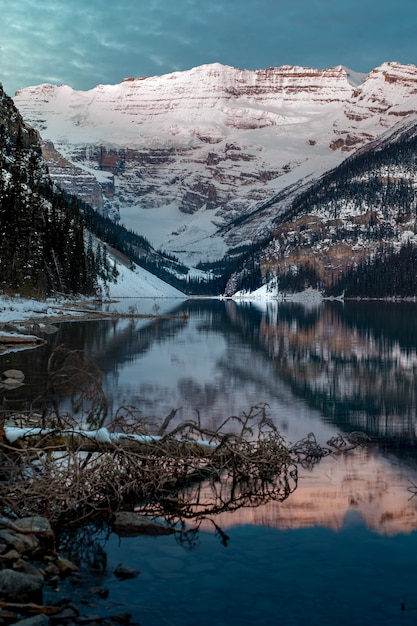 Vertical shot of the snowy mountains reflected in the lake louise in canada Free Photo