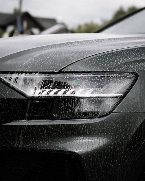 Vertical shot of soap on a black shiny modern car at daytime Free Photo
