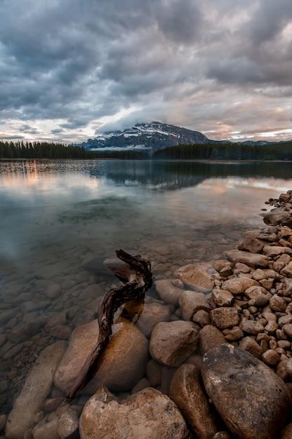 Colpo verticale delle pietre nel lago trasparente sotto il cielo nuvoloso scuro Foto Gratuite