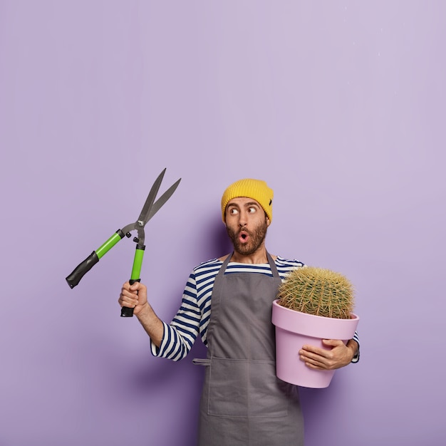 Vertical shot of surprised male gardener holds pruning shears Free Photo