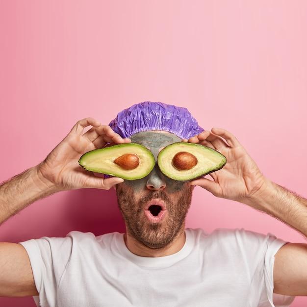 Il colpo verticale dell'uomo sorpreso tiene le fette di avocado sugli occhi per la procedura di cura della pelle, applica la maschera di argilla di bellezza, utilizza le proprietà curative della frutta Foto Gratuite