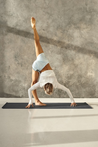 Vertical shot of tanned athletic young man working out in gym doing variation of standing split or urdhva prasarita eka padasana against grey wall. fit sporty guy practicing advanced yoga indoors Free Photo