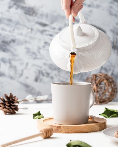 Colpo verticale di un tè che versa da un bollitore a una tazza bianca con un cucchiaio di legno Foto Gratuite