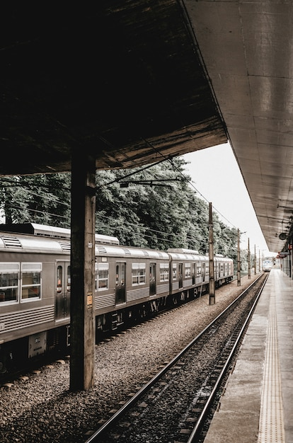 Vertical shot of a train stop with a grey metallic train leaving Free Photo