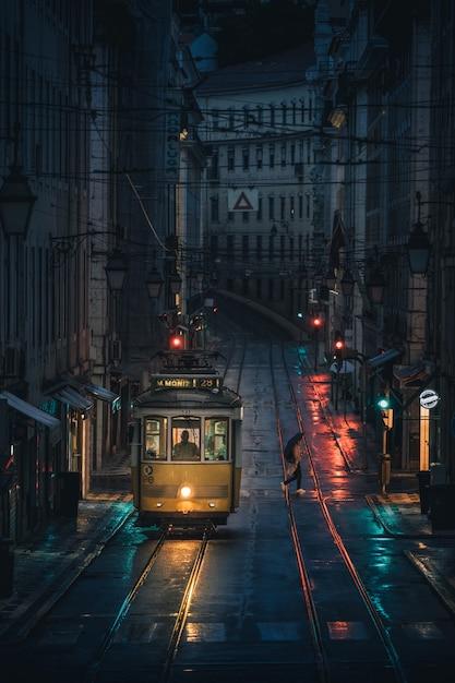 Colpo verticale di un tram che attraversa gli edifici di una città durante la notte Foto Gratuite