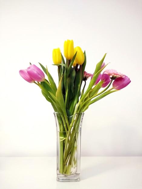 Colpo verticale di un bouquet di tulipani in un vaso sul tavolo sotto le luci Foto Gratuite