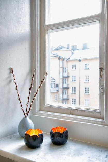 Inquadratura verticale di due esclusivi portacandele e un vaso con una pianta d'appartamento vicino alla finestra Foto Gratuite