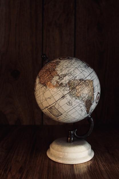 Colpo verticale di un modello di globo vintage su un tavolo di legno con una parete di legno in background Foto Gratuite