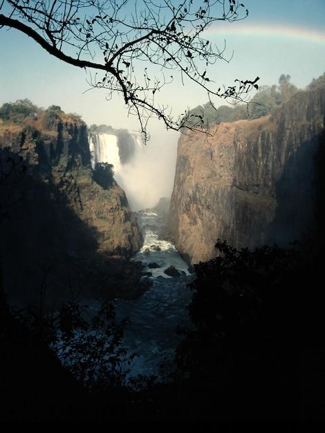 Colpo verticale di un flusso d'acqua nel mezzo di scogliere e una cascata in lontananza Foto Gratuite