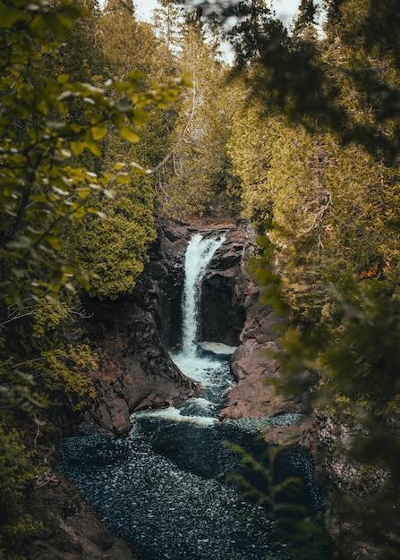 Colpo verticale di una cascata che scorre lungo il ruscello vicino a rocce e piante Foto Gratuite