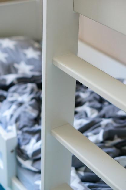 Colpo verticale di una scala in legno bianca vicino al letto Foto Gratuite