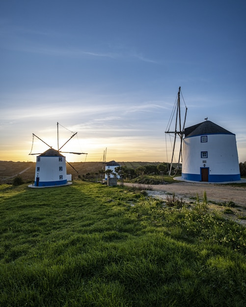 Vertical shot of windmills with a sunrise in a clear blue sky in the background Free Photo