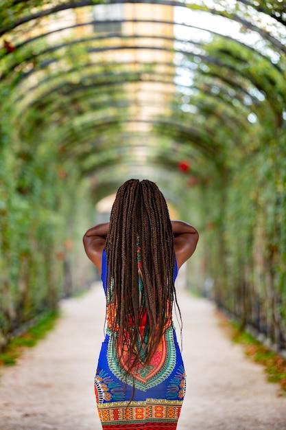 Colpo verticale di una donna in un bellissimo corridoio di decorazione floreale Foto Gratuite