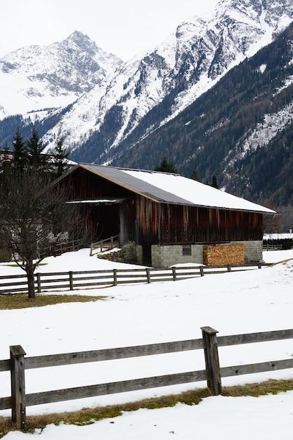 Colpo verticale di una casetta in legno ricoperta di neve e montagne in inverno Foto Gratuite