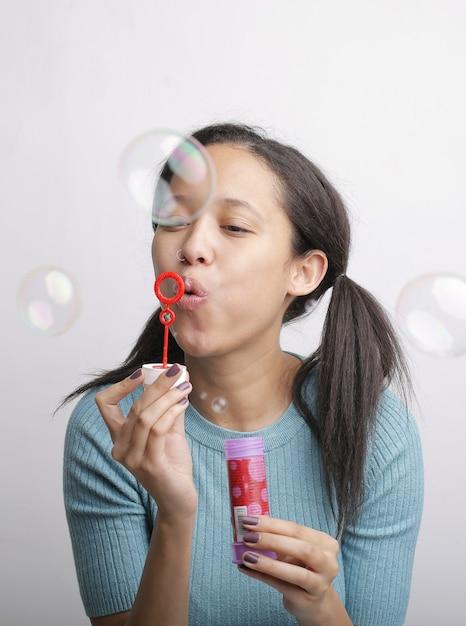 Colpo verticale di una giovane donna che soffia bolle di sapone Foto Gratuite