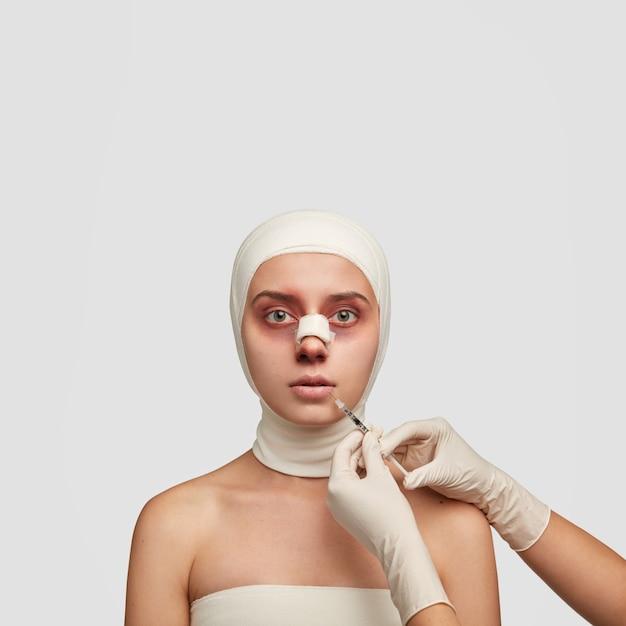 Colpo verticale di giovane paziente femminile che subisce un intervento di chirurgia plastica del naso, ha bende mediche sulla testa Foto Gratuite