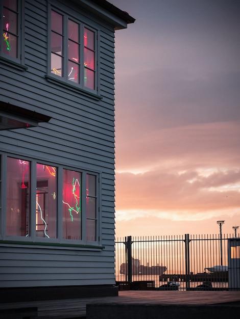 Vista verticale di una bella casa in legno con decorazioni alle finestre vicino al mare Foto Gratuite