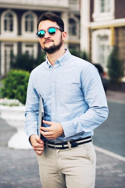 垂直ビューサングラスのブリティッシュクォーターを歩くハンサムなひげを生やした実業家。 無料写真