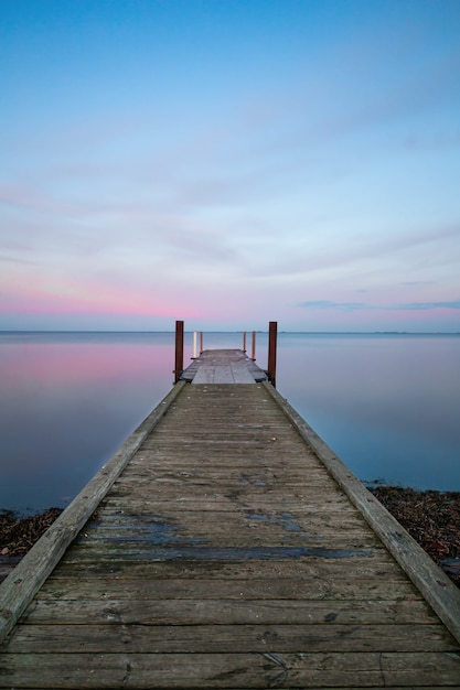 Vertical view of a long wooden pier near the ocean under the pastel-colored sky Free Photo