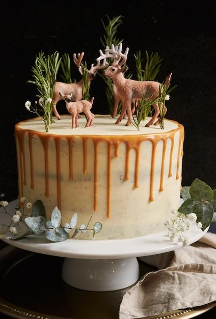 白いクリームとオレンジ色のしずくと森とトナカイが上にある夢のようなケーキの垂直方向のビュー 無料写真