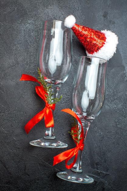 赤と黒の表面にクリスマスサンタクロース帽子ガラスゴブレットの垂直方向のビュー 無料写真