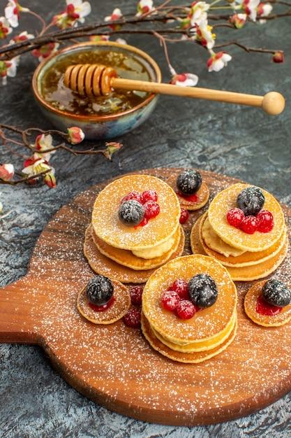 灰色のボウルに古典的なアメリカのパンケーキ蜂蜜の垂直方向のビュー 無料写真