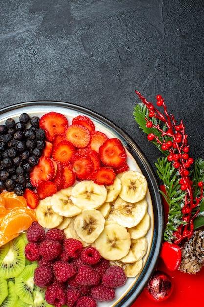 ディナープレート装飾アクセサリーモミの枝と黒い背景の上の赤いナプキンの数字の新鮮な果物のコレクションの垂直方向のビュー 無料写真