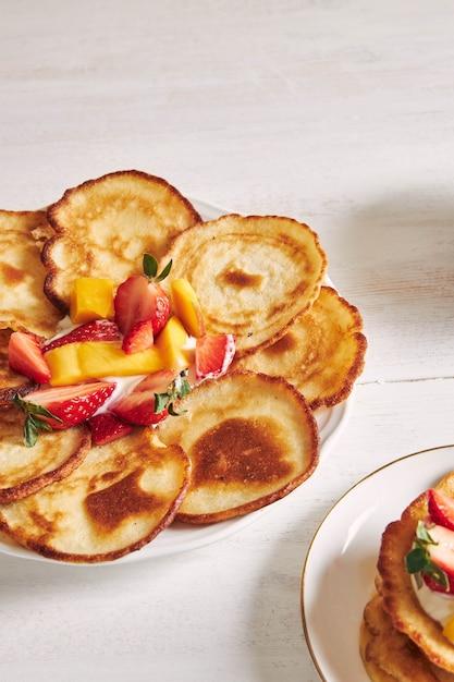 白い木のテーブルの上の果物とおいしいパンケーキの垂直方向のビュー 無料写真