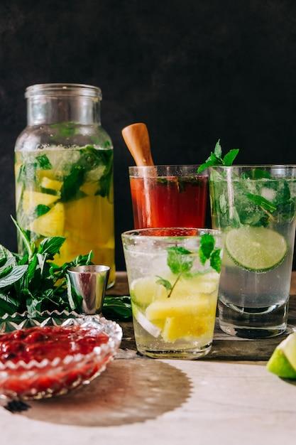 Вертикальный вид свежеприготовленных холодных напитков с фруктами и мятой на столе Бесплатные Фотографии