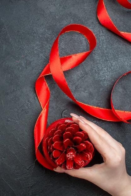 Вертикальный вид руки, держащей шишку с красной лентой на темном фоне Бесплатные Фотографии