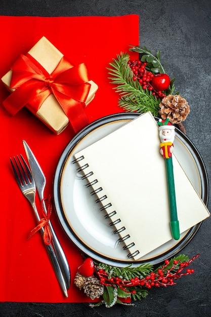 빨간 냅킨에 선물 옆 디너 플레이트 칼 붙이 세트 장식 액세서리 전나무 가지에 나선형 노트북으로 새 해 배경의 세로보기 무료 사진