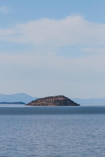 Vista verticale del mare che circonda un'isola sotto il cielo nuvoloso durante il giorno Foto Gratuite
