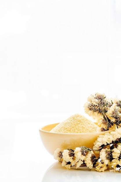 Vertical view yellow cup of yellow scrub powder wiht yellow flower Premium Photo
