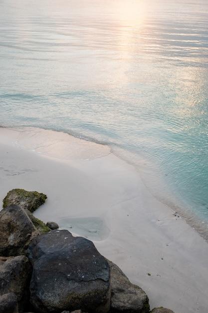 Colpo verticale di una spiaggia sabbiosa con il riflesso del sole nell'acqua blu Foto Gratuite