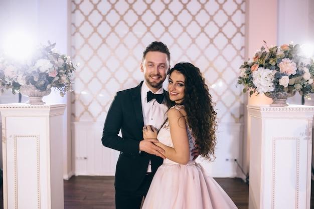Очень красивые и счастливые молодожены стоят возле красиво украшенной свадебной арки на своей свадебной церемонии. Premium Фотографии