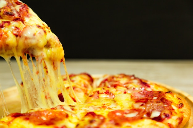 Very cheesy pizza slice in hand.hot pizza slice with melting cheese Premium Photo