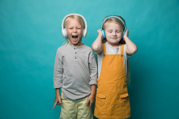Very emotional children listen to music with headphones on a blue . Premium Photo