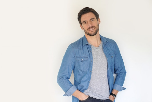 Very handsome casual man smiling and standing with hands in pocket Premium Photo