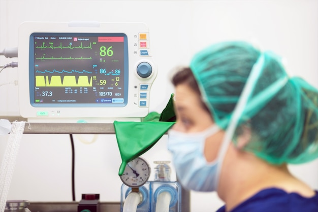 Veterinarian doctor portrait in operating room. anesthesia monitoring in the background Premium Photo