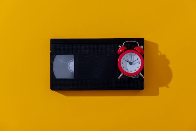 黄色の背景に赤い目覚まし時計とvhsカセット Premium写真