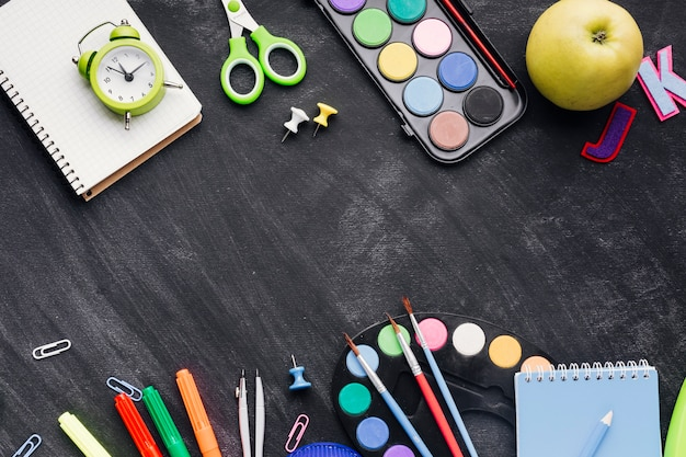 Vibrant stationery, clock and apple on grey background Free Photo