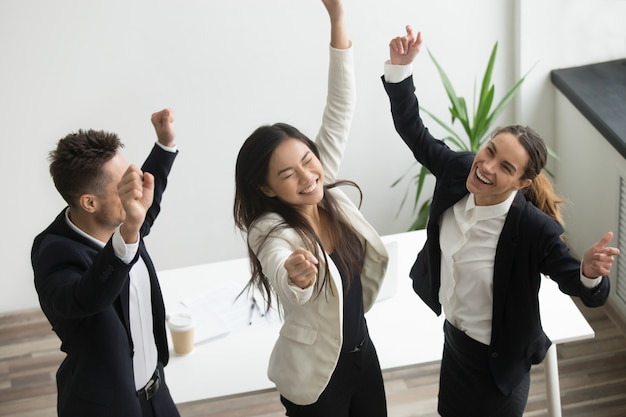 Victory dance concept, excited diverse coworkers celebrating business success Free Photo