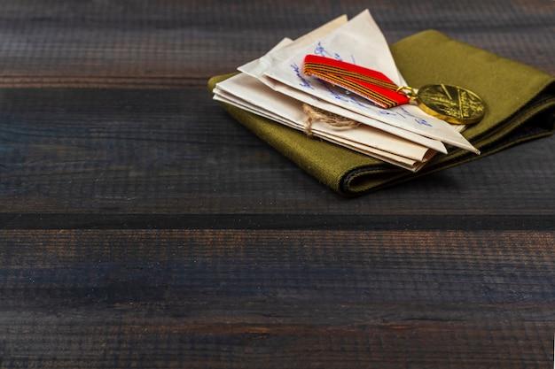День победы фон - 9 мая 1945 года. св. фронтовые письма, военная гарнизонная шапка и ордена на деревянном фоне. вид сверху, скопируйте пространство для текста Premium Фотографии