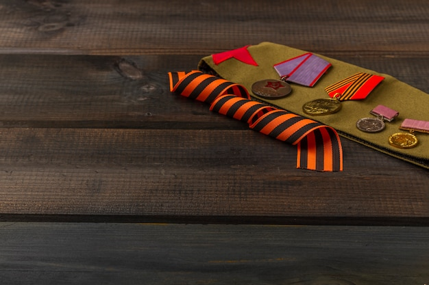 Фон победы - 9 мая 1945 года. георгиевская ленточка, фронтовые письма, военная гарнизонная шапка и ордена на деревянном фоне. вид сверху, скопируйте пространство для текста Premium Фотографии