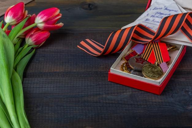 День победы фон. георгиевская ленточка, фронтовые письма, военная гарнизонная шапка и ордена на деревянном фоне. Premium Фотографии